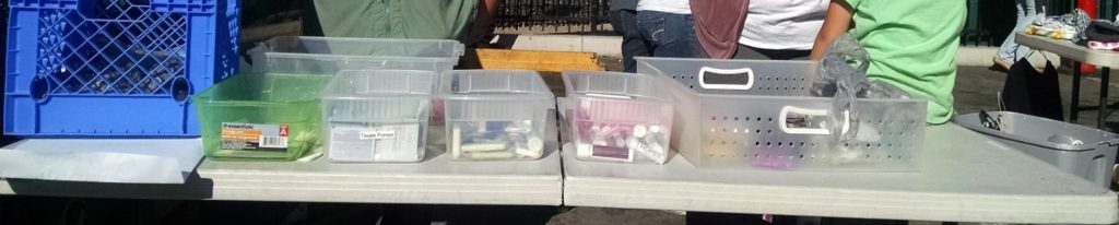 Tampons, shampoo, soap, tooth brushes, and other hygiene supplies in plastic bins